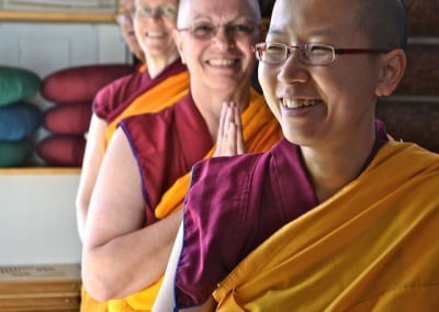Buddhist nuns with folded hands, smiling.