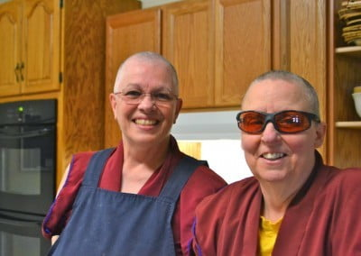 Two Buddhist nuns smile at the camera.
