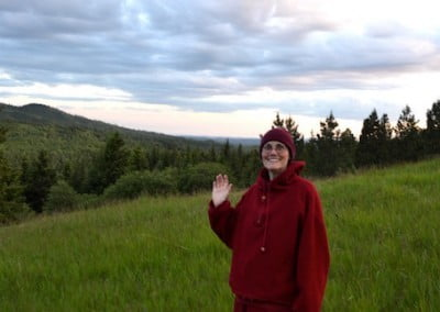 A nun, standing on a grassy hill, waves at the camera