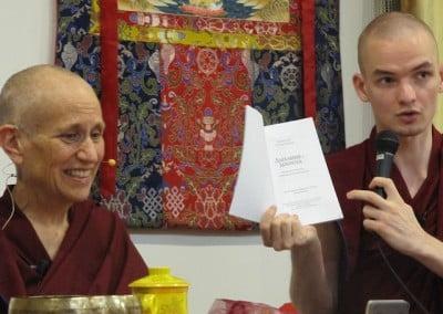 A Buddhist nun smiling, a Buddhist monk holding up an open book.