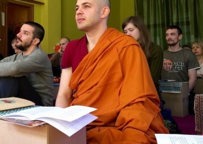 A Buddhist nun surrounded by lay students listens attentively.
