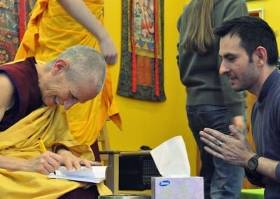 A Buddhist nun signs a book while a man looks on.