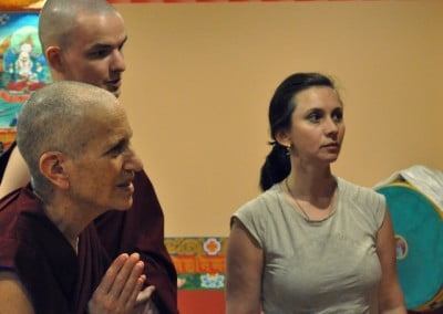 Two monastics and a woman listening