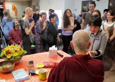 A Buddhist nun sits behind a table with students standing around her.
