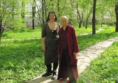 A Buddhist nun and a lay woman on a path surrounded by greenery