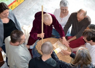 Using a thin wood stick, Venerable Chodron taps the blessed objects<br> and incense to create a level bottom to re-attach the copper base.