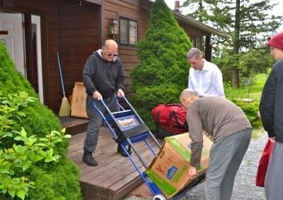 Volunteers help move heavy boxes.