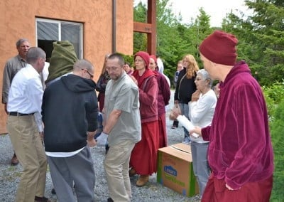 Venerable Chodron leads the way with an incense offering as we carefully carry the covered Buddha inside.