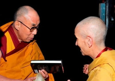 Venerable Thubten Chodron offers the book to His Holiness  backstage at the Beacon Theatre in New York.