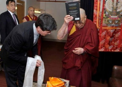 Wisdom Publications' CEO, Tim McNeil, offers a copy to His Holiness at an event in Boston.