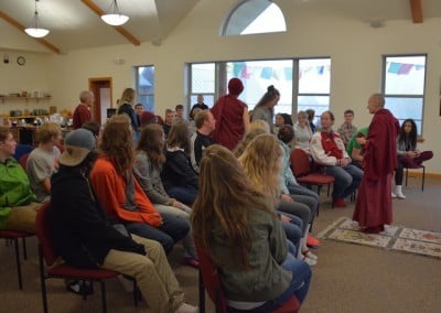 Men and women sitting in rows waiting inside the dining room, set up for a Dharma talk.