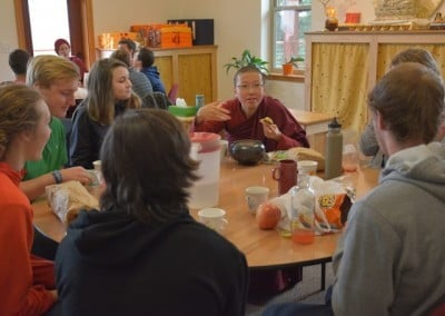 Buddhist nun, Venerable Damcho holding a piece of food in her hand talking to students on a round table where fruits, cups and chips are placed.