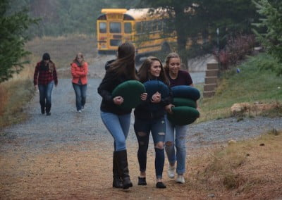Three girls carrying cushions in their hands, walking on a stone path.