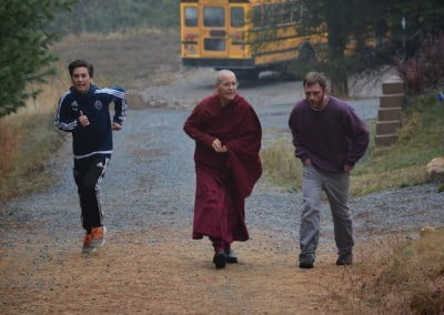 Buddhist nun, Venerable Semkye walking with a guy on the stone path, while a young boy is running beside them.