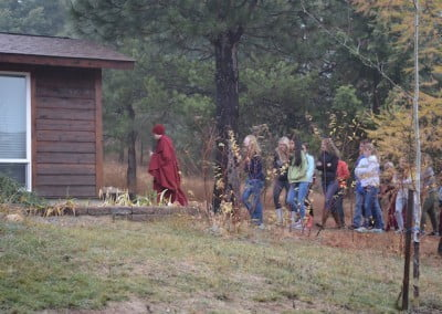 A buddhist nun leading in front, followed by a group of students, walking to the Meditation Hall