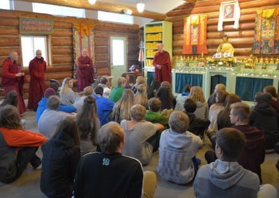 Students all seating on the floor of the Meditation Hall while four buddhist nuns are standing by the side.