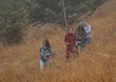 Buddhist nun, Venerable Jampa and three young girls walking downhill through long yellow grasses.