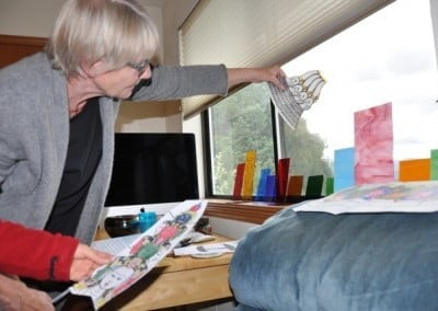Bev shows the group the colored glass she will use in the stained-glass <br> window of Chenrezig that she is making.
