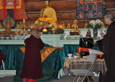Ruby offers incense to the Buddha.