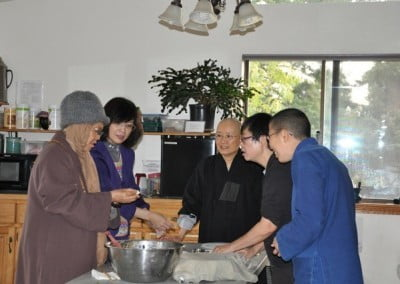 Venerable Minjia shares her skill at making spring rolls with the kitchen team.