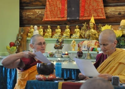 Chanting Tara's mantra, the Green Tara retreatants all take part as Ven. Chonyi gives Ven. Chodron the closing papers to sign.