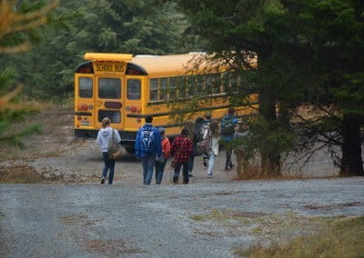Girls and boys carrying their school bags, walking down the stone path towards the yellow bus.