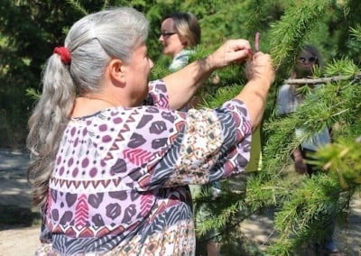 Kathy ties her note of wishes and  prayers to the aspiration <br> tree.