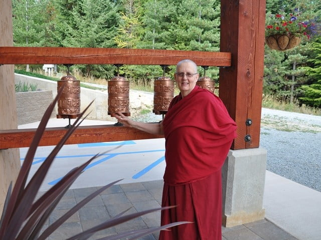 Venerable Thubten Jigme turns the prayer wheels, sending prayers out onto the wind.