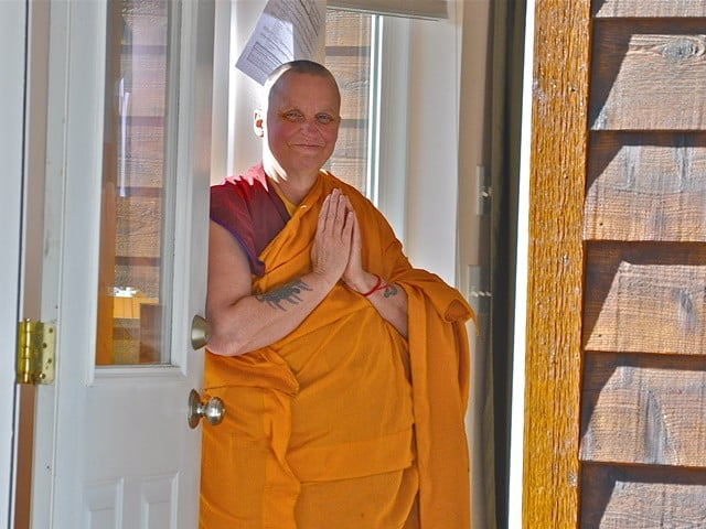 Venerable Thubten Tsultrim waits at the door to greet our guests coming to the Meditation Hall.