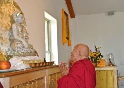 Geshe Thabkhe makes a khata offering to the Buddha.