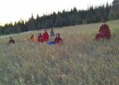 The community meditates on the meadow during the night of the lunar eclipse.