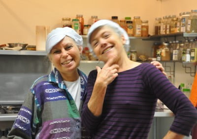 Two women with white kitchen hats in front of the spice rack.