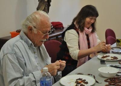 A man and woman making malas.