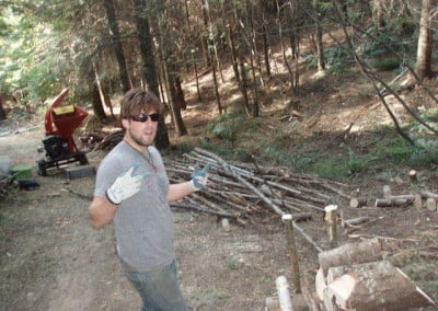A man in the forest with a stacks of wood and a red machine behind him.