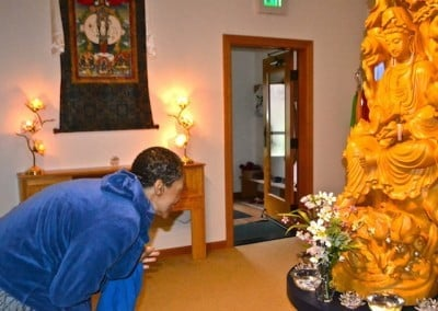 A woman bowing at a wooden Guan Yin statue.