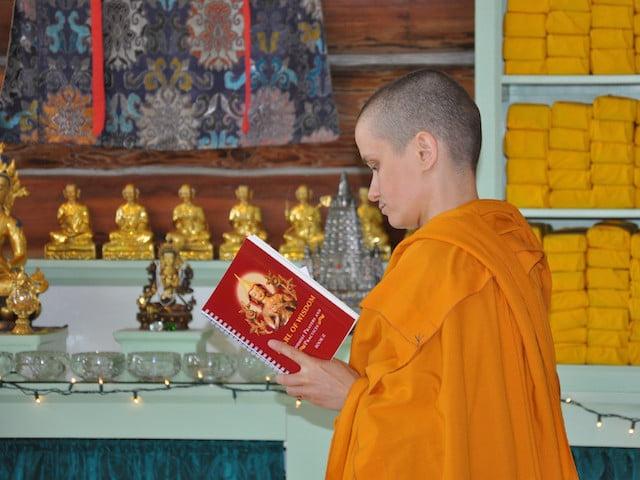A buddhist nun looking at a buddhist book.