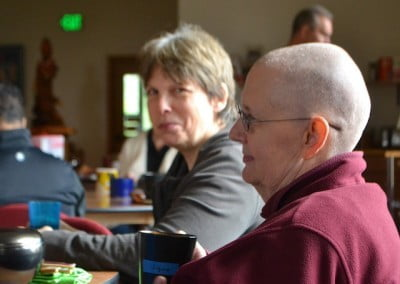 Side view of buddhist nun, Venerable Jigme taking a cup in her hands.