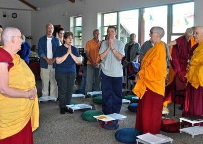 Abbey buddhist nuns, laymen and laywomen standing and chanting.