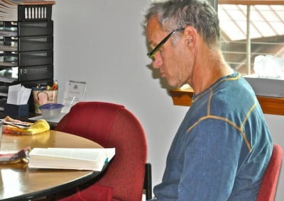 Man sits at dining room table and looks down at a book as he studies the Dharma