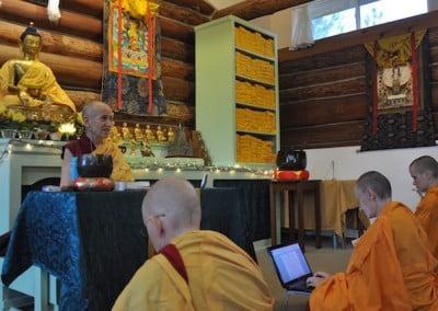 Buddhist nun, Venerable Chodron giving a Dharma talk, buddhist nuns sitting on the floor listening. Venerable Samten typing on a laptop.