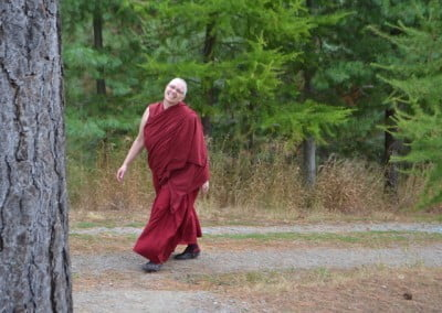 Buddhist nun, Venerable Yeshe smiling and walking on a stone path.