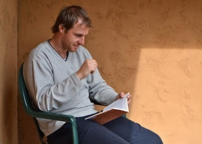 A man sitting alone on a chair reading a book with concentration.
