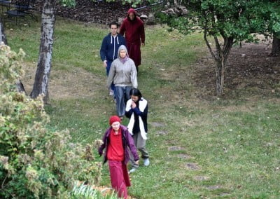 Two buddhist nuns, two women and a man walking on a forest trail.