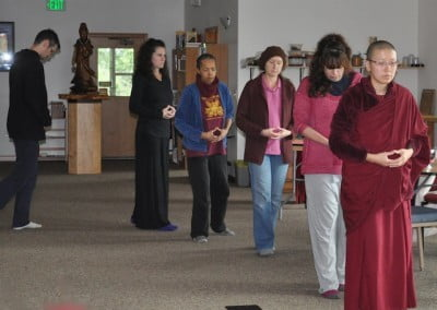 Buddhist nun, Venerable Damcho leading a walking meditation with four women and a man.