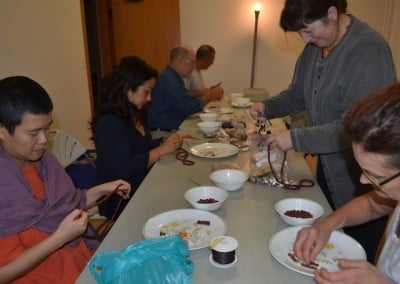 Tracy organizes a crew to string prayer beads for prison Dharma practitioners.