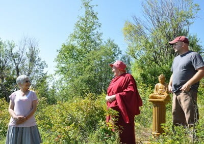 Buddhist nun, Jigme talking to a woman while a man was standing beside a Buddha statue.