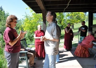 A man and a woman talking to each other in the foreground, buddhist nun in the background talking to lay people.