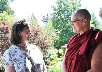 A woman smiling at buddhist nun, Yeshe.