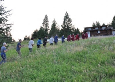 The group walks the perimeter of the building site chanting Om Mani Padme Hum.