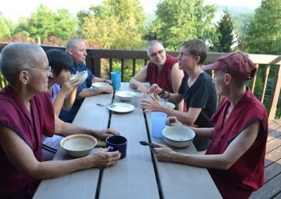 Buddhist nuns, one anagarika and a young lady all looking at a man who is talking.